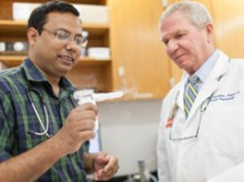 Dr. Mondal (l) and Hendeles demonstrate an asthmanefrin atomizer, the device that turns the liquid racemic epinephrine into a mist that is inhaled by an asthma patient. The mist can  be seen coming from the mouthpiece.
